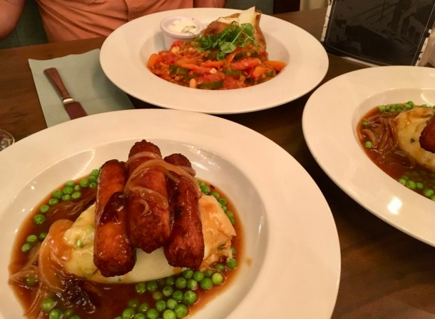 Traditional Irish food (bangers and mash) made vegan + gluten-free: jackfruit sausages, mashed potatoes, peas, onions, and mushroom gravy.