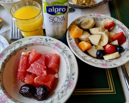 One bowl of mixed fruit, another of grapefruit and dates, along with orange juice and soy milk.