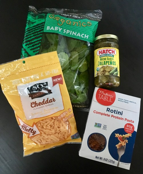 This photo shows four ingredients to make mac and cheese: (1) bag of baby spinach; (2) So Delicious dairy-free cheddar shreds; (3) a jar of nacho sliced jalapenos; and (4) rotini pasta made from lentils, rice, and peas.