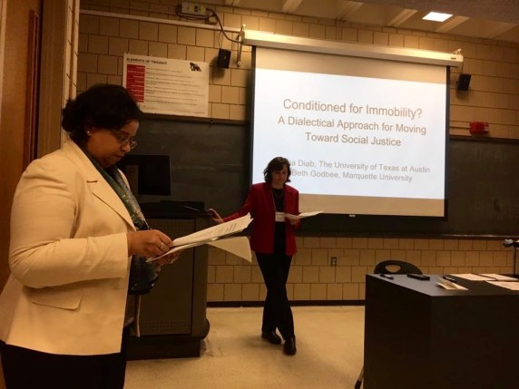 This photo from the 2016 Watson Conference shows the two of us—Rasha Diab (left) and Beth Godbee (right)—co-presenting: both with heads down, reading notes, standing at the front of a classroom.