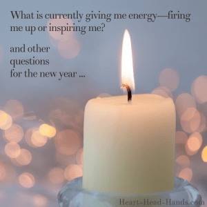 "This image reads ""What is currently giving me energy—firing me up or inspiring me? and other questions for the new year …"" against a light blue-gray background. A cream-colored candle and flame appear with pink-peach glowing dots. Attribution to Heart-Head-Hands.com appears in the lower right-hand corner."