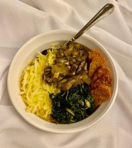 Bowl of sautéed greens, spaghetti squash, mushroom gravy, and these tempeh sticks.