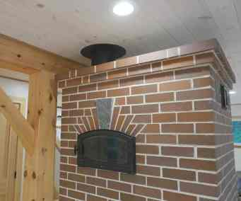 Bake oven faces the kitchen on this brick masonry heater.  Project design and management by Homestead Heat.