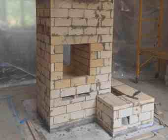 "double-bell masonry heater core showing ""see-through"" firebox and heated bench. project lead by Homestead Heat."