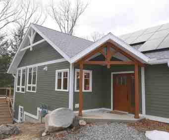 custom timber trusses accent gable ends and front porch of custom home