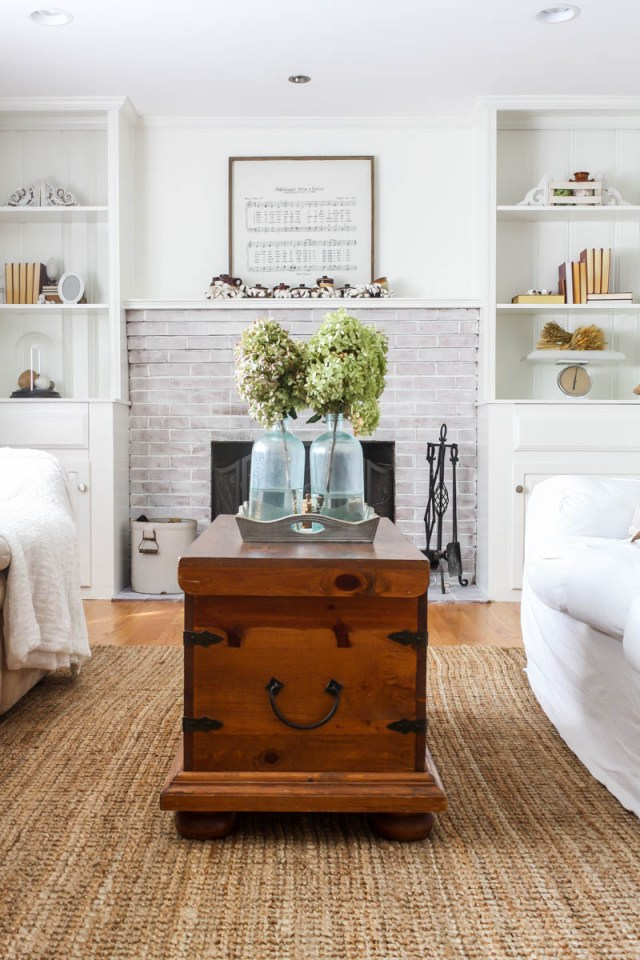 Living room fire place. built in cabinets around fired place. Wood burning fireplace. Dough Bowl decor. Window wall decor. DIY dropcloth slip cover. How to bleach dropcloth. dried hydrangeas. blue glass mason jar.