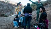 A U.S. Border Patrol agent speaks to the women and children who crossed illegally into San Ysidro, Calif., on December 2. Ariana Drehsler/UPI photo