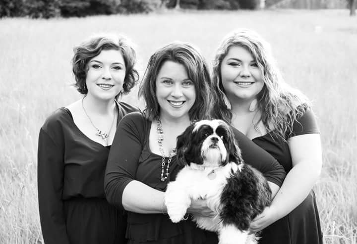 Black and white photo of three people with a shih tzu