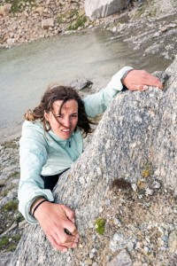 Woman climbing up a cliff - struggling alone