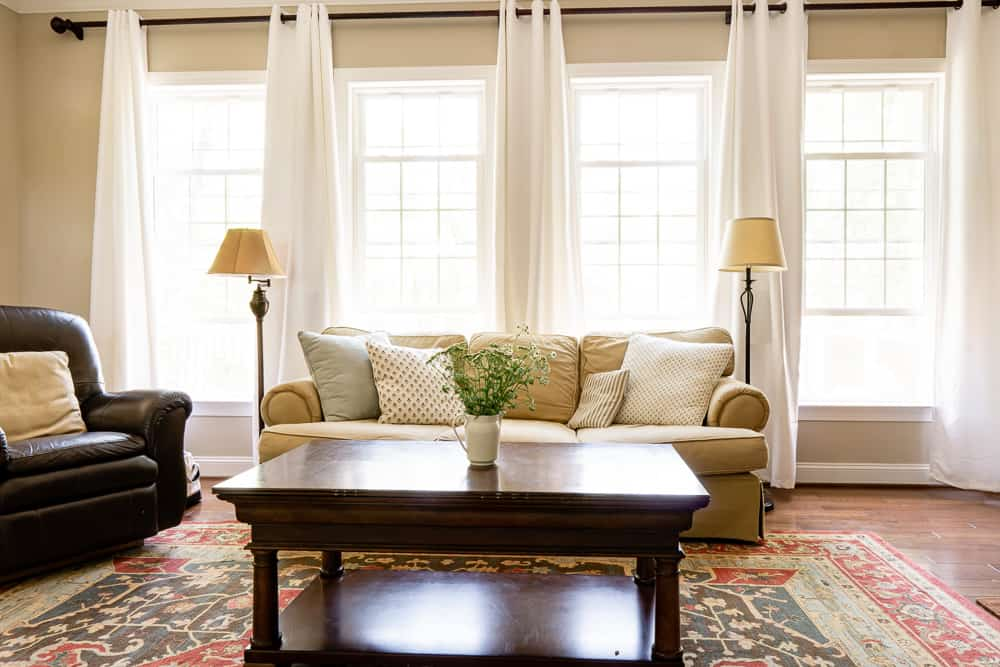 budget decorated living room with white curtains and beige furniture