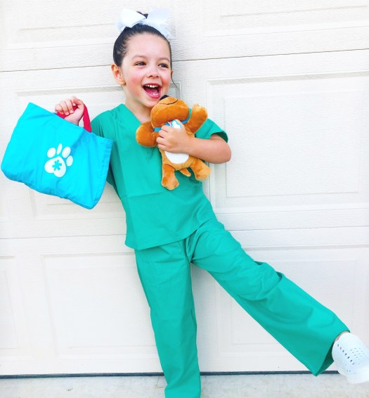 child dressed up as a vet holding a stuffed dog and vet kit