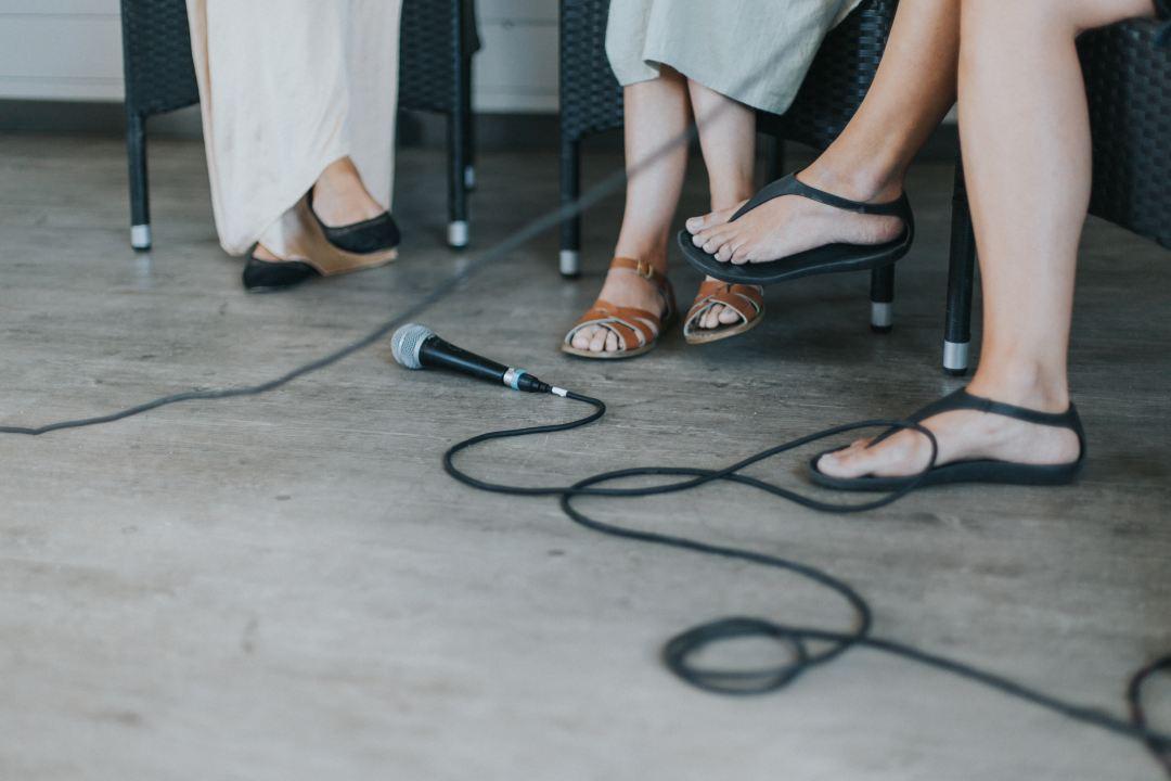 microphone by feet of women sitting around