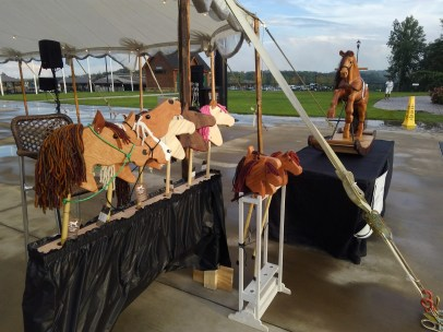 hand made hobby horses and large oak rocking horse set up at picturesque scene during sunset at the Saturday Night Lights Tryon International Equestrian Center Gran Prix