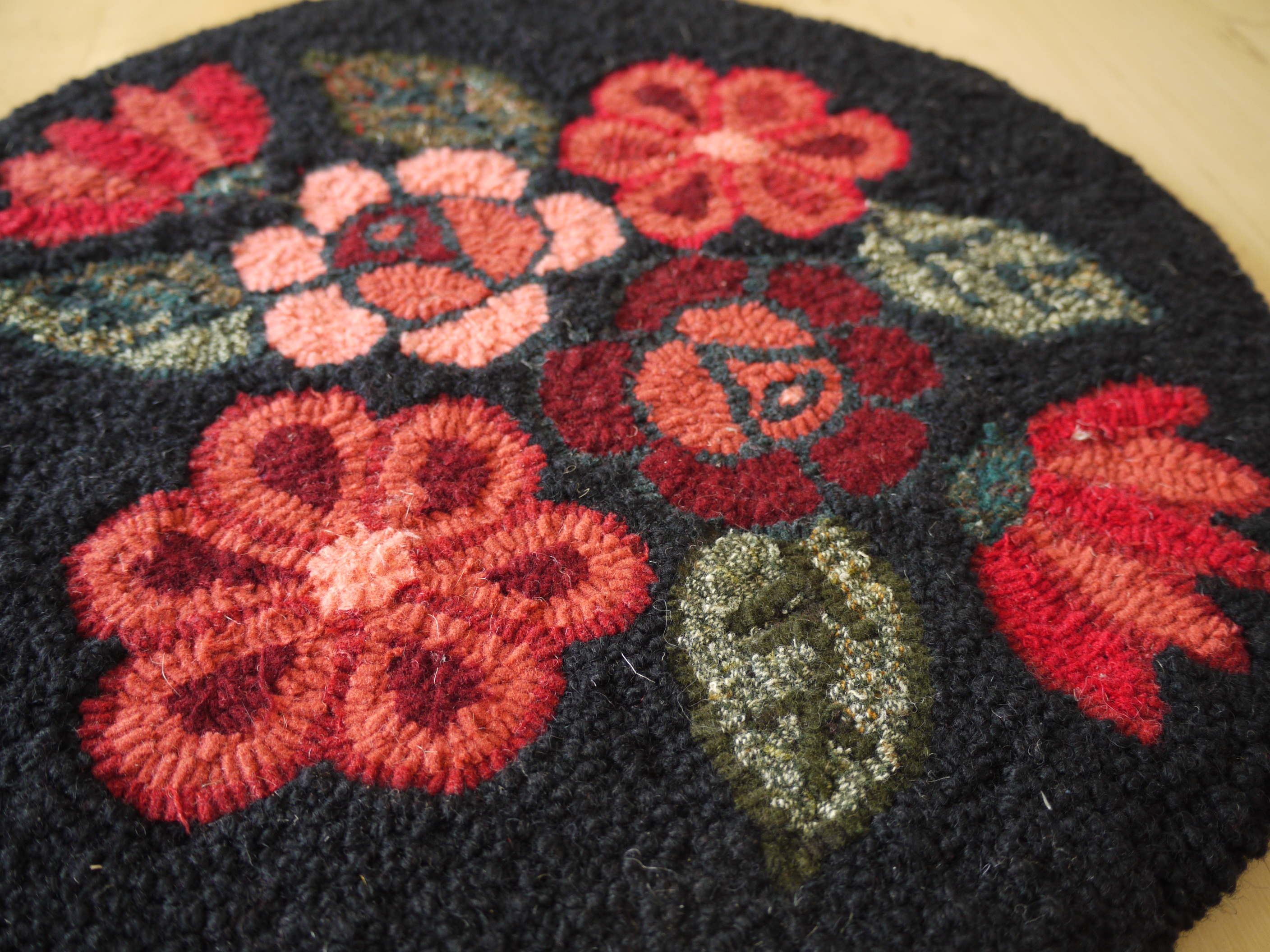 black hooked mat with coral flowers.