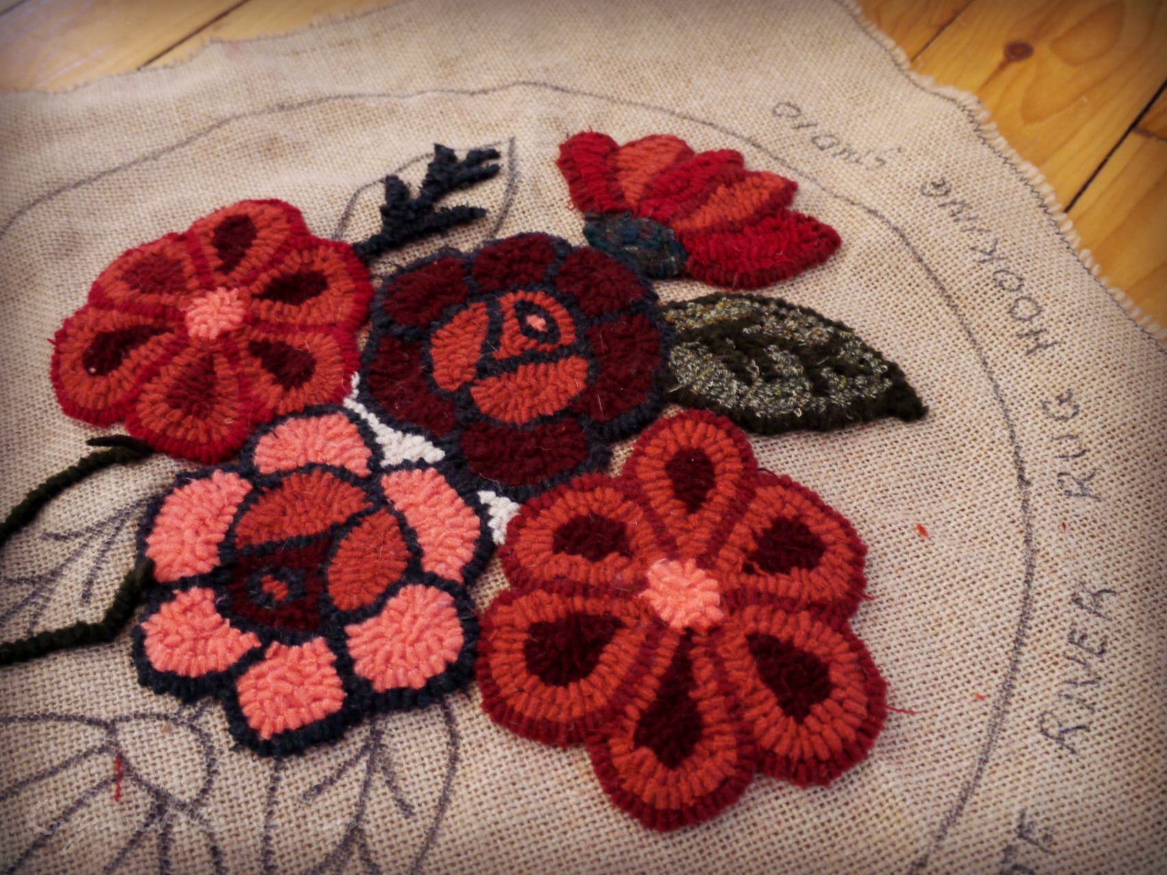 Floral mat in progress. Flowers hooked with wool strips.