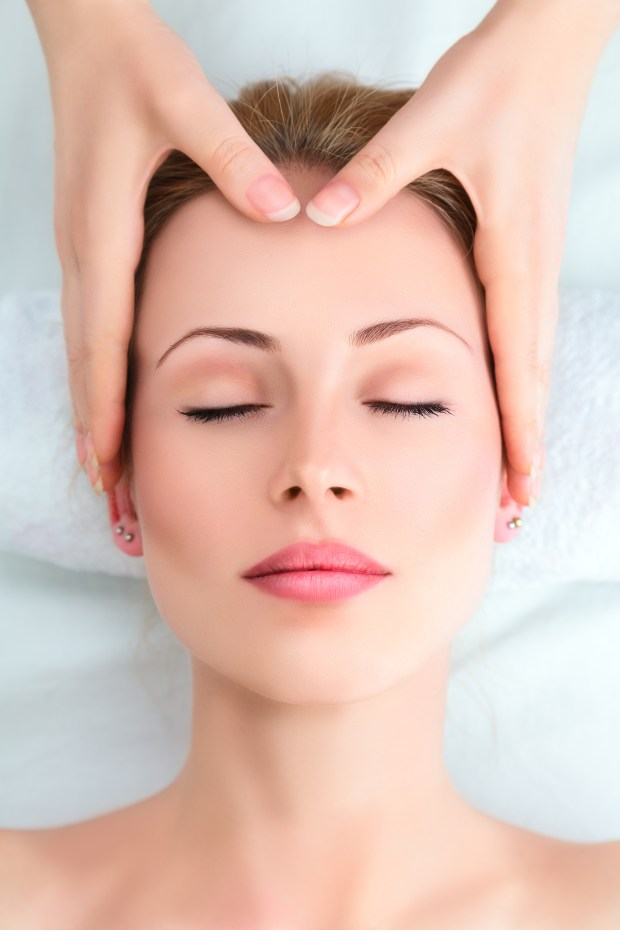 Hands massaging woman's forehead during facial