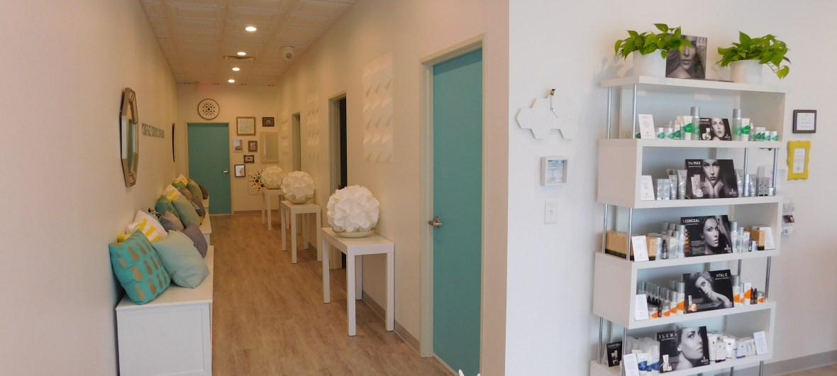 Heather Brown Face and Body Studio front interior hallway with white and blue decor, beauty products on display.
