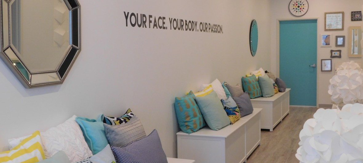 "Benches with pillows inside Heather Brown Face and Body Studio. Wall reads ""Your Face. Your Body. Our Passion."""