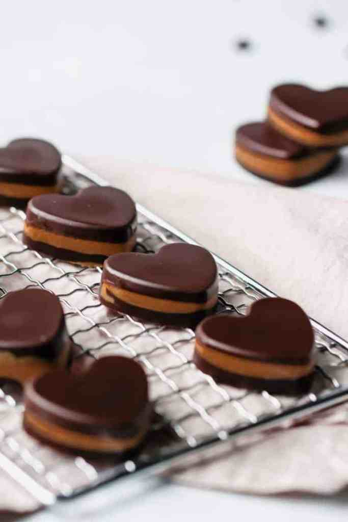 Heart shaped keto peanut butter cups on a cooling rack.