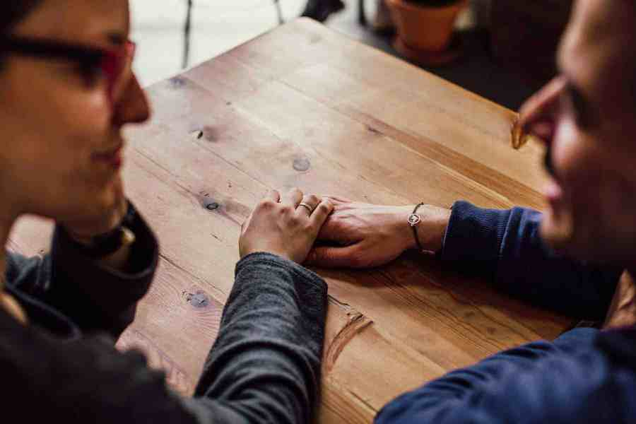 Man and woman holding hands on a table top - Emotional Responses to a Cancer Diagnosis