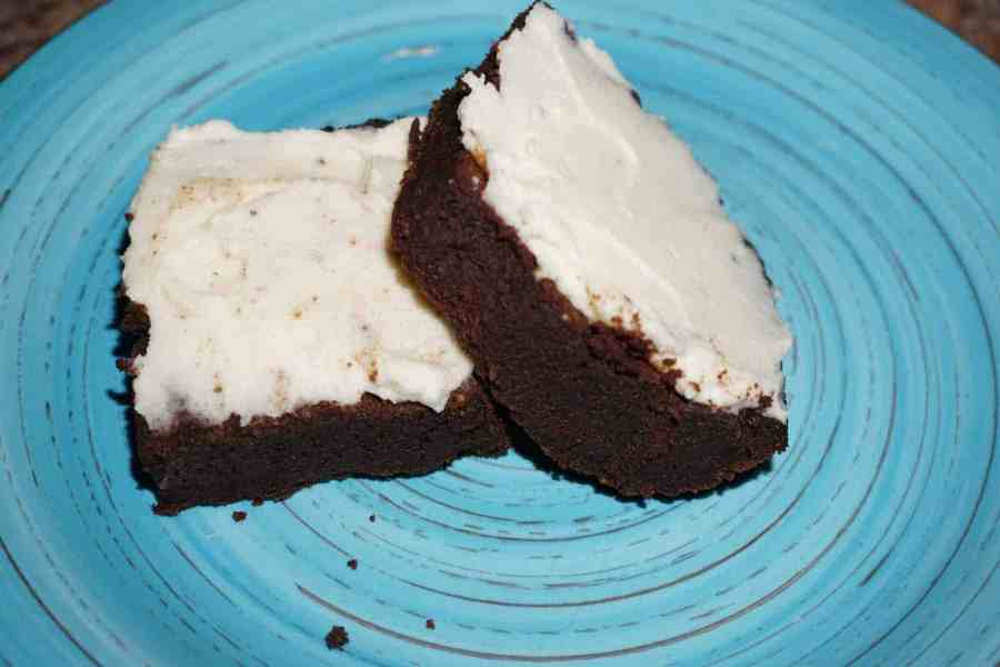 Ultimate fudge keto brownies with keto cream cheese frosting on a plate.