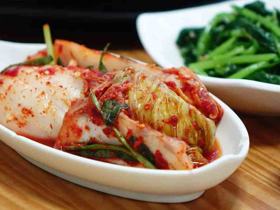 Fermented foods: Kimchi in a dish on table next to dish of green beans.