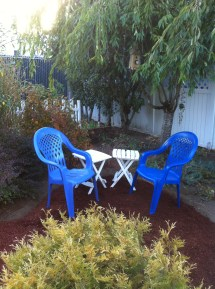 Two blue chairs and two small white tables sit in a garden.