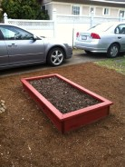 A red stained raised bed sits in a front yard near two cars.