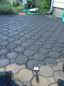 Back patio paving stones being painted a dark gray brown color.
