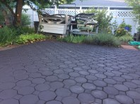 Freshly painted patio paving stones glisten wetly, with plants and yard decor in background.