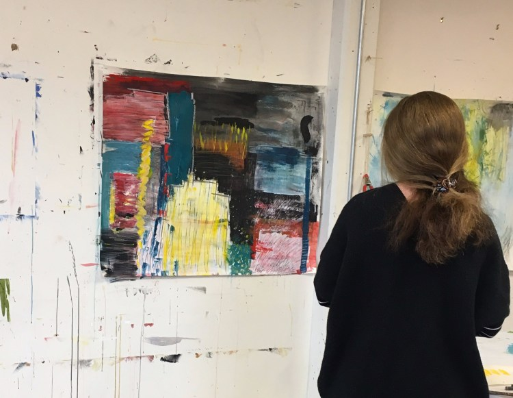 Student contemplating her art