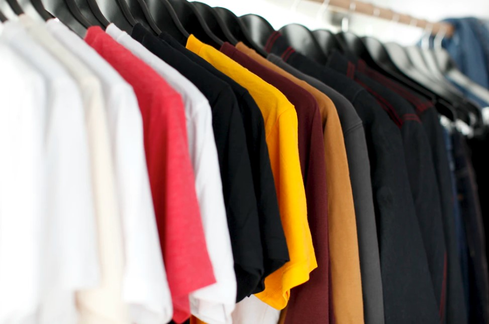 tshirts of different colors, white, black, yellow, and red, hanging on hangers
