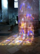 sunlight through stained glass window reflected on wall of Gloucester cathedral
