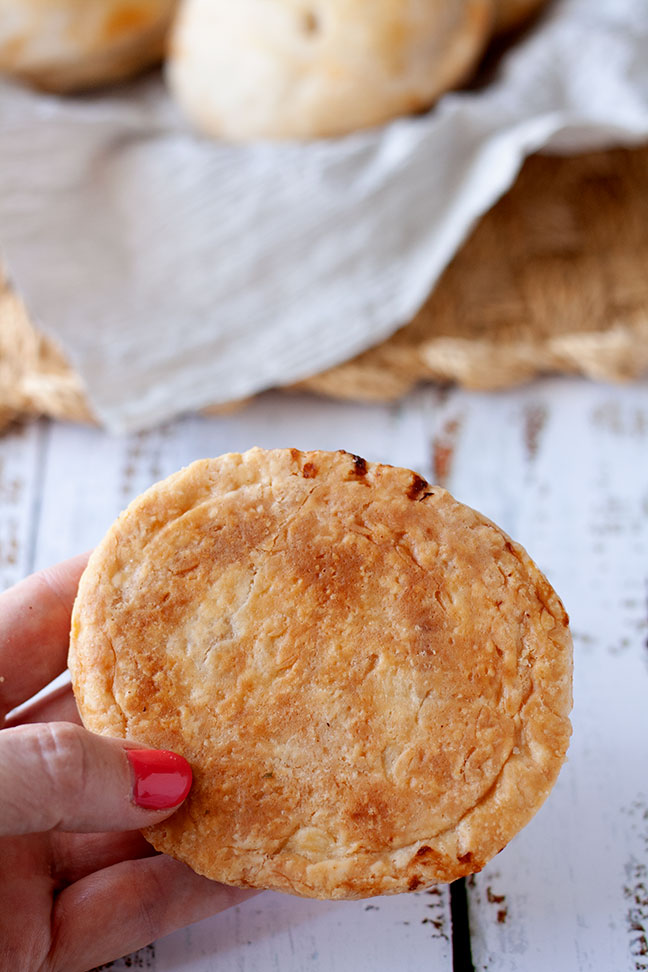 A hand showing the underside of a baked mini pie.