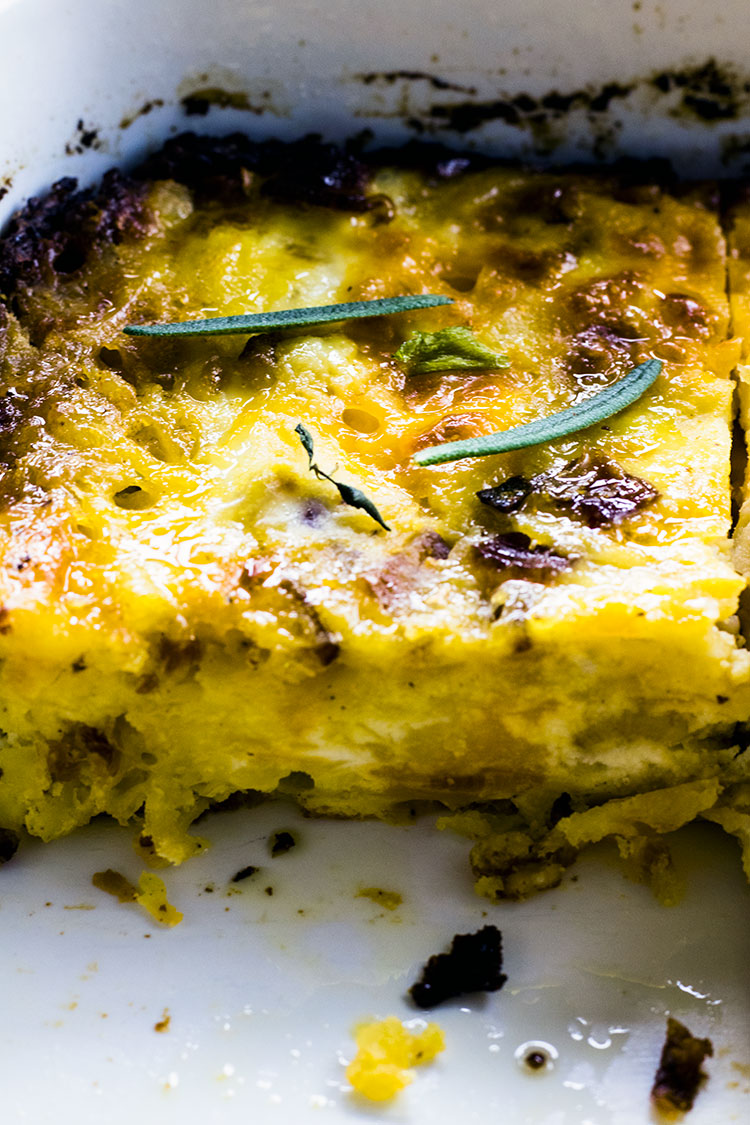 Close up of egg, potato and cheese breakfast casserole garnished with rosemary leaves sitting in a white casserole dish with slice taken out