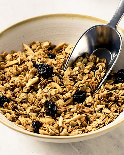 A bowl of granola with a metal scoop.