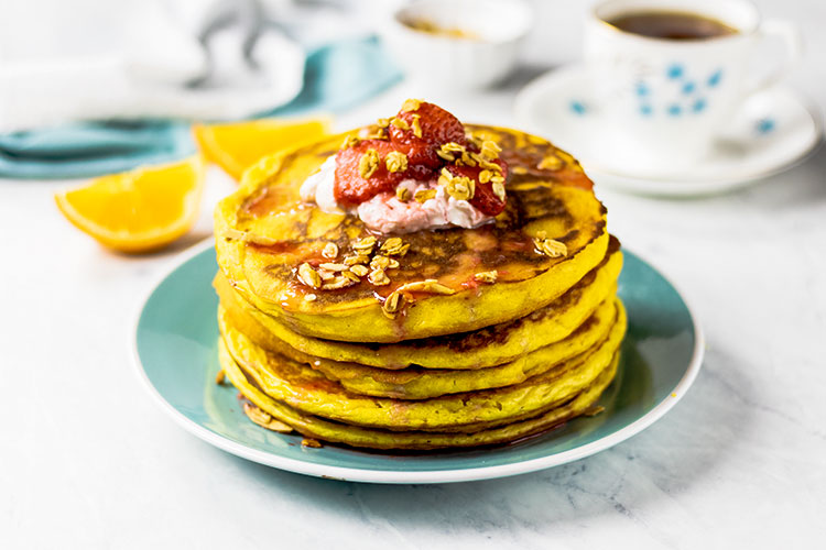 Stack of orange pancakes sitting on a turquoise plate topped with yogurt, fresh strawberries and homemade granola. Fresh oranges, a turquoise and white napkin and cup of coffee or tea are in the background.