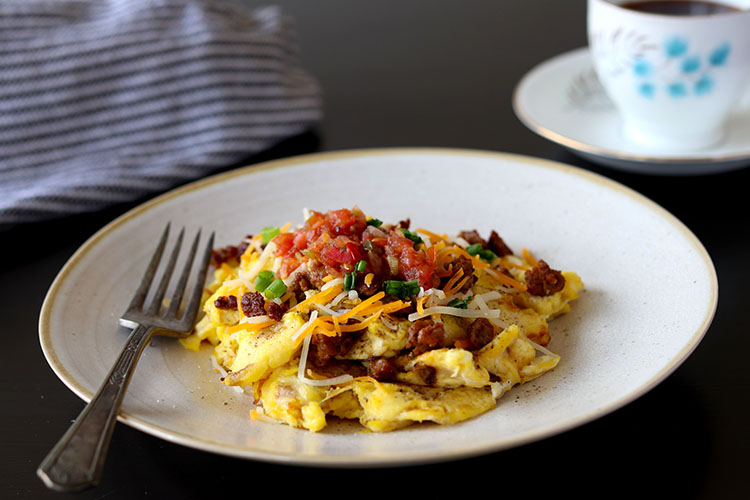 A close up view of scrambled eggs and salsa on a plate.