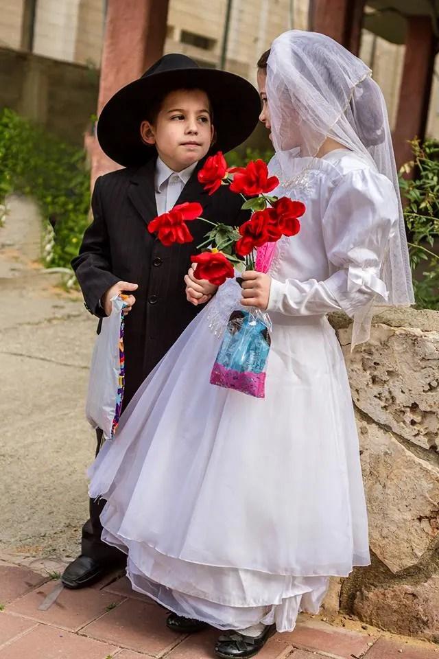 ילד וילדה מחופשים לחתן וכלה חסידים