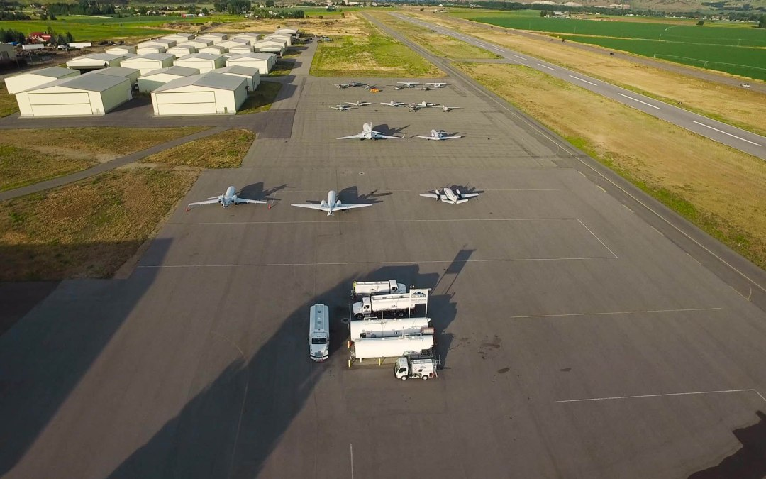 Aerial shot of ramp at Heber Airport with jets parked and small airplane hangars in the background