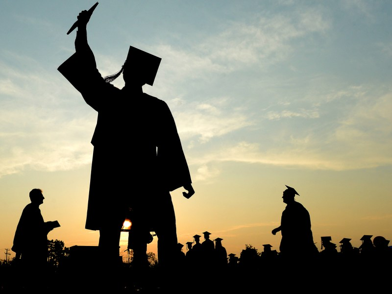 A high school graduate raises his diploma in celebration as he walks back to his seat during a commencement ceremony Wednesday, June 10, 2015, in Pittston, Pa.