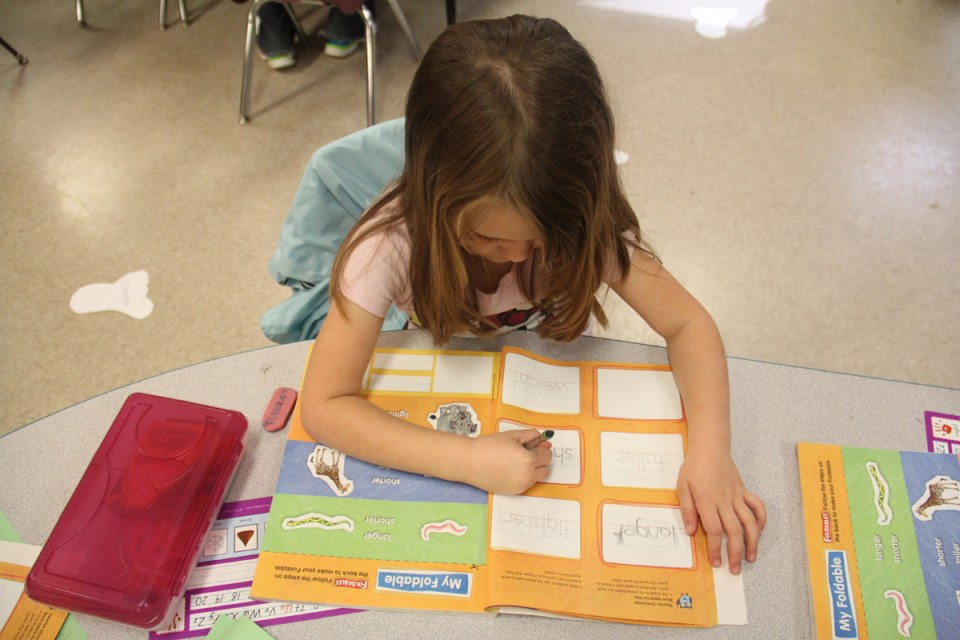 A student in Lynn Chapman's kindergarten class works on a workbook lesson about height.