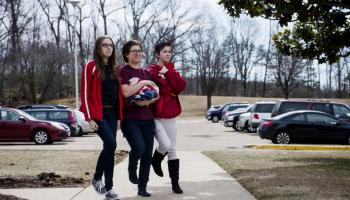 From left: Meghan Meza, Meghan Jones, and Summer Gilliard, return to the school after lowering the flags at Quantico Middle/High School on March 13, 2015 in Quantico, VA.
