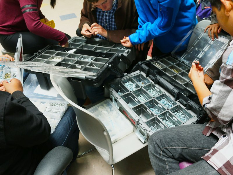 Ninth grade students organize nuts and bolts the day after their end-of-the-year showcase in which they flew their school-made drones for parents and visitors.