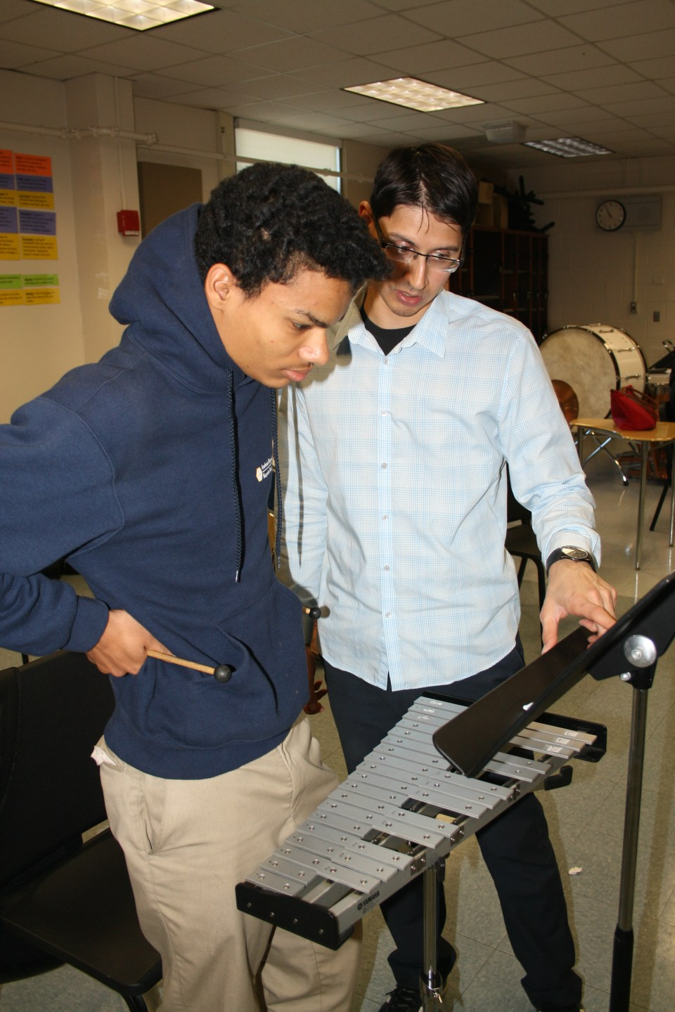 Margarita Muñiz Academy music teacher Avi Mehta helps a student master a piece on the xylophone.