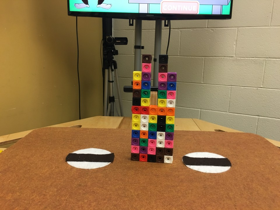 A tower of blocks on Nesra Yannier's earthquake table during an experiment at Forest Grove Elementary School.