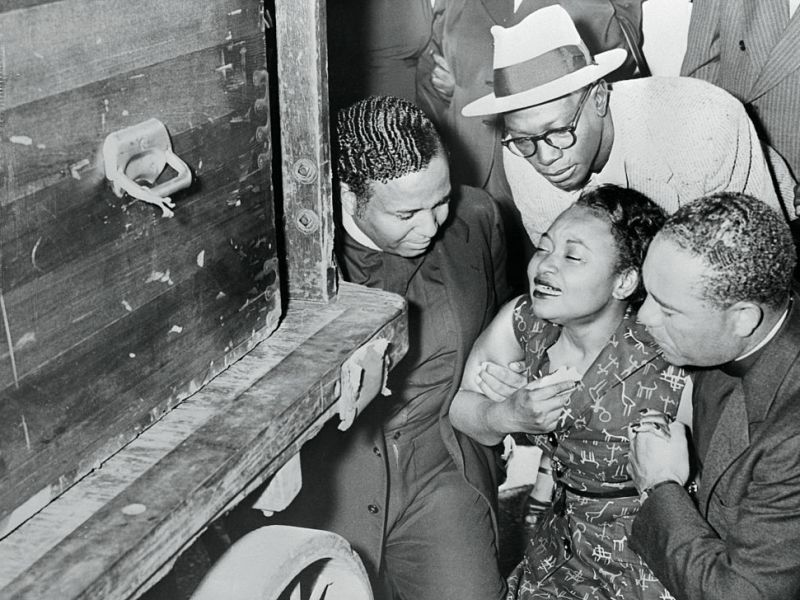 Sinking to knees, Mrs Mamie Bradley weeps as body of slain son, Emmett Louis Till, 14 arrives at Chicago Rail Station.