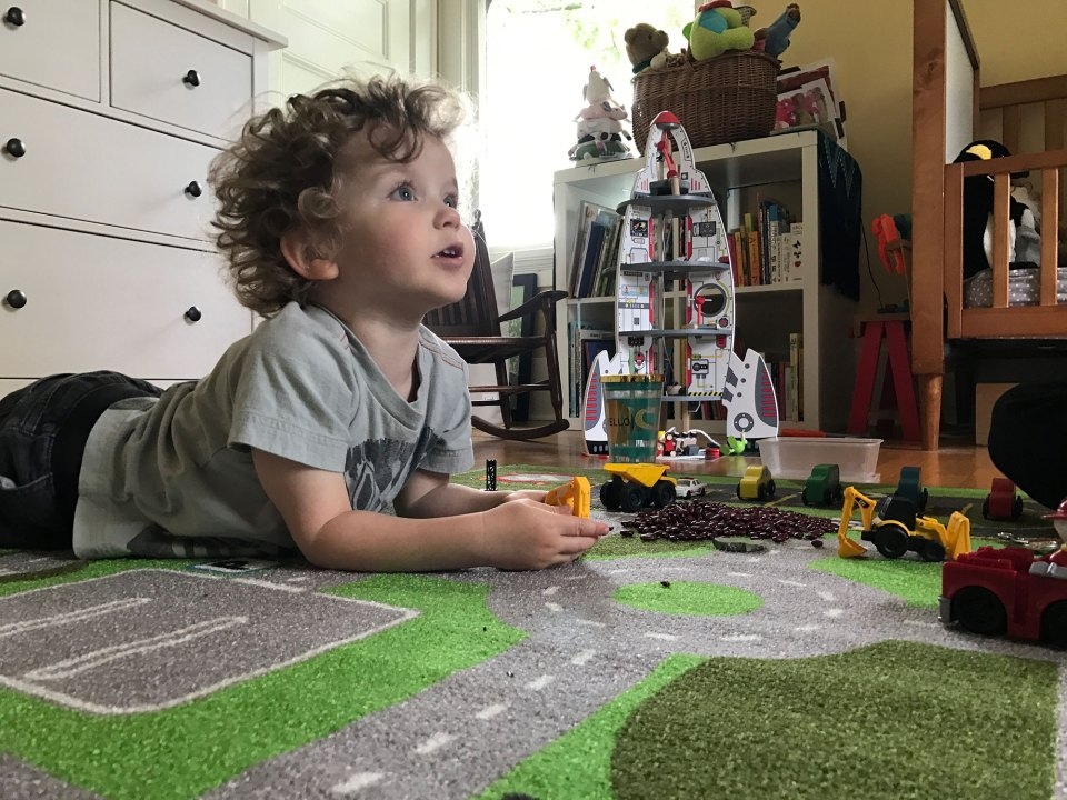Clark Tinker, age 2 in this photo, looks up from playing with his toy truck to listen to his mother ask him a question.