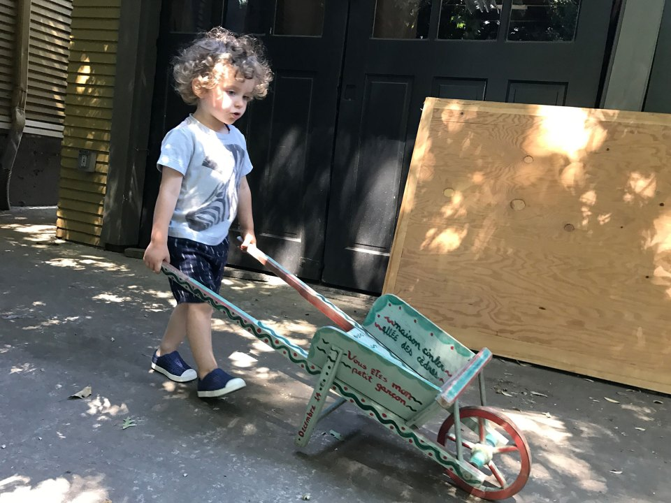 Pushing a toy wheelbarrow across his driveway is one of dozens of new gross motor skills Clark Tinker, age 2 in this photo, has mastered recently. Gross motor skills are important for the cognitive development of young children.