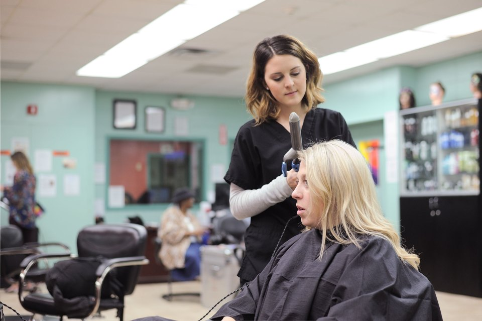 Jessie Green, 22, curls 19-year-old fellow student Jordan Brown's hair in a practice salon for cosmetology students at West Georgia Technical College.